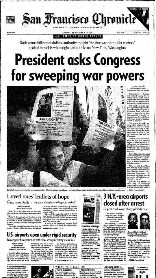 """The front page of The San Francisco Chronicle on Sept. 14, 2001 shows a woman holding missing person fliers under the headline """"President asks Congress for sweeping war powers."""""""