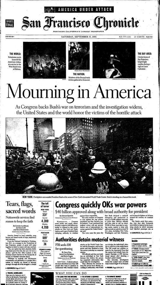 """The San Francisco Chronicle front page from Sept. 15, 2001 shows President Bush surrounded by New York firefighters under the headline """"Mourning in America."""""""