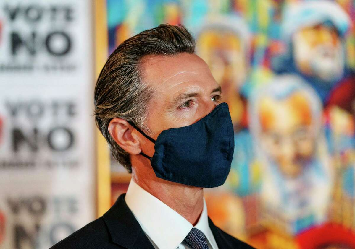 """California Governor Gavin Newsom listens to others speakers during a press conference at Manny's in San Francisco on August 13, 2021 for the """"Vote No"""" campaign opposing his recall in the upcoming election."""