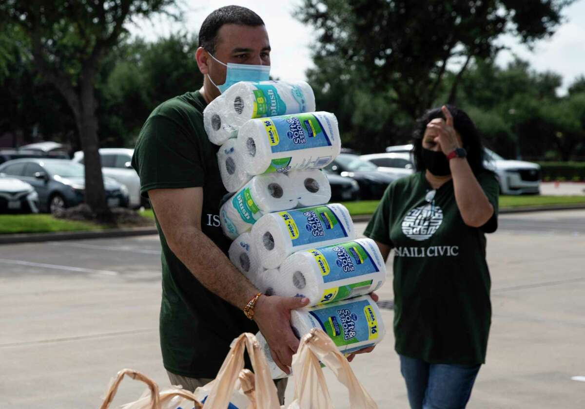 Volunteer Raj Thakur unloads a stack of toilet paper at a supply drive for Afghan refugees and survivors of the earthquake in Haiti at the Ismaili Jamatkhana and Center Saturday, Aug. 28, 2021, in Sugar Land.