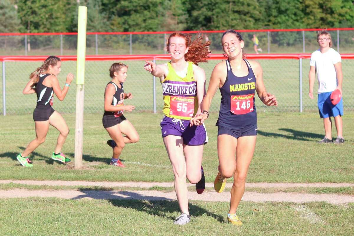 Frankfort's Taylor Myers helps steer Manistee's Cecelia Postma back on course, even at the expense of her friend Postma going on to narrowly beat her to the finish on Sept. 1. (Robert Myers/News Advocate)