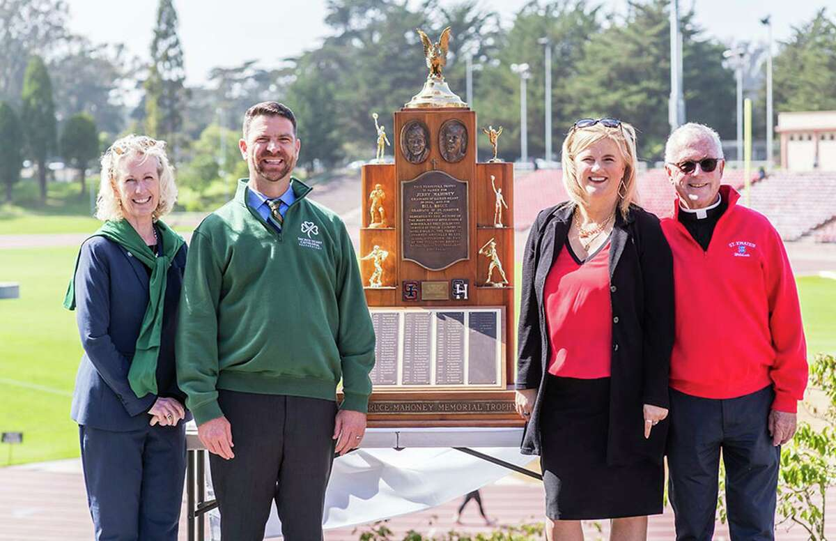 Sacred Heart Cathedral President Melinda Lawlor Skrade, left, and Principal Gary J. Cannon, second from left, frame the Bruce-Mahoney Memorial Trophy with St. Ignatius Principal Michelle Nevin Levine, second from right, and the Rev. Edward A. Reese, school president.