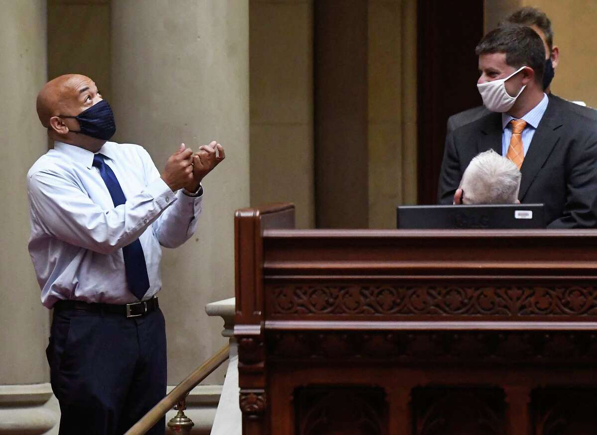 New York state Assembly Speaker Carl Heastie, D-Bronx, left, speaks with aids while on the floor of the Assembly chamber during a special legislative session to extend pandemic era eviction protections in the wake of a Supreme Court decision lifting the moratorium at the state Capitol, Wednesday, Sept. 1, 2021, in Albany, N.Y. (AP Photo/Hans Pennink)
