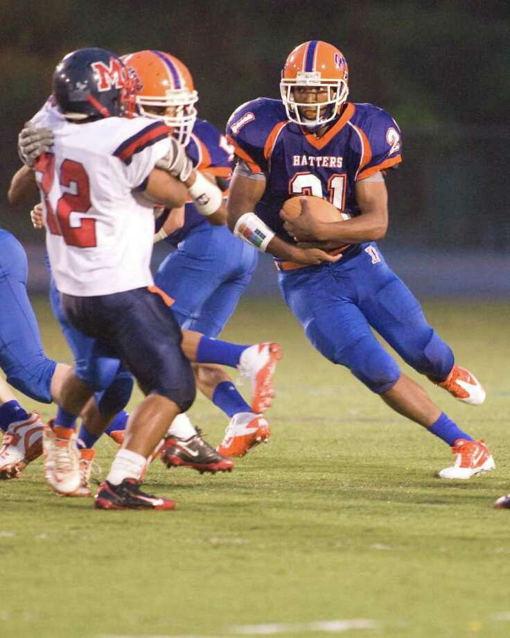 Danbury High School's Deyon Rosado (21) takes advantage of a block from Marcus Dixon on Brien McMahon's Ryan Eaton (32) to pickup yardage Thursday night, Sept. 16, 2010, at Danbury High School. Photo: Barry Horn / The News-Times Freelance