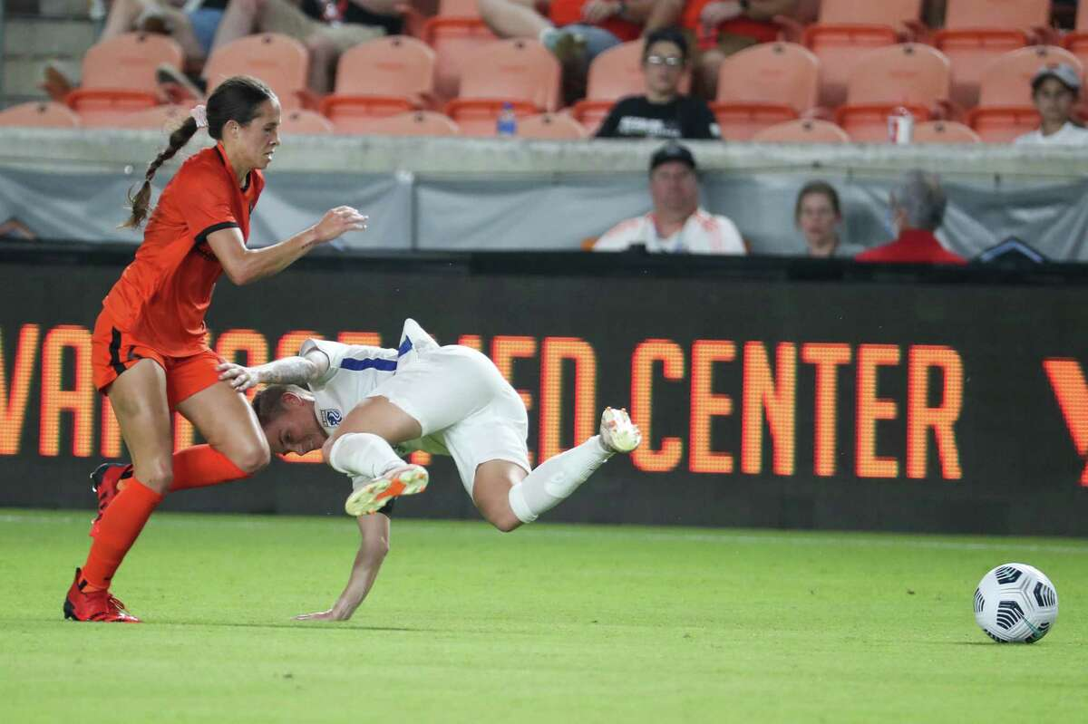 Dash midfielder Shea Groom (left) gets tangled up with OL Reign midfielder Jess Fishlock going after a loose ball during the second half of Houston's 1-0 loss Wednesday at BBVA Stadium.