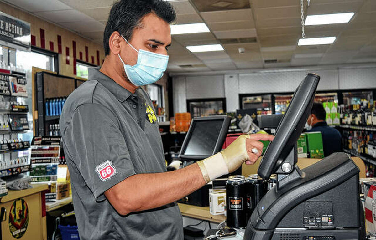 A manager at AM PM operates the cash register in the convience store at the newly opened gas station in South Jacksonville.