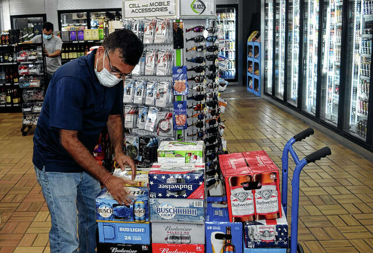 Everest Thapa, owner of AM PM South Jacksonville gas station, stocks beer Wednesday in the convenience store.