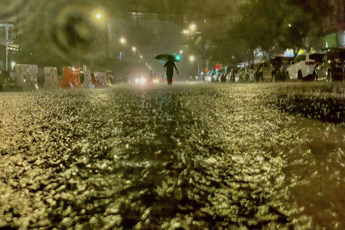 A person makes their way in rainfall from the remnants of Hurricane Ida on September 1, 2021, in the Bronx borough of New York City. The once category 4 hurricane passed through New York City, dumping 3.15 inches of rain in the span of an hour at Central Park.
