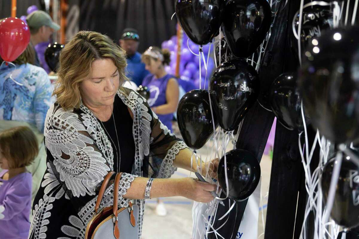 A woman attaches a balloon to an art installation during an event hosted on International Overdose Awareness Day by Montgomery County Overdose Prevention Endeavor at the Youth Building at StoneBridge Church this week in The Woodlands. Black balloons carried the names of victims of substance-abuse related deaths and were used to honor them.