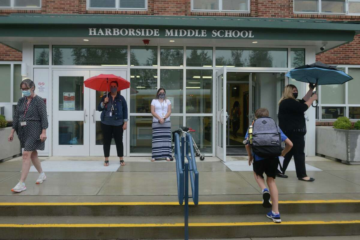 Students arrive for the first day of class at Harborside Middle School, in Milford, Conn. Sept. 1, 2021. The school closed on Thursday due to flooding caused by the remnants of Hurricane Ida.