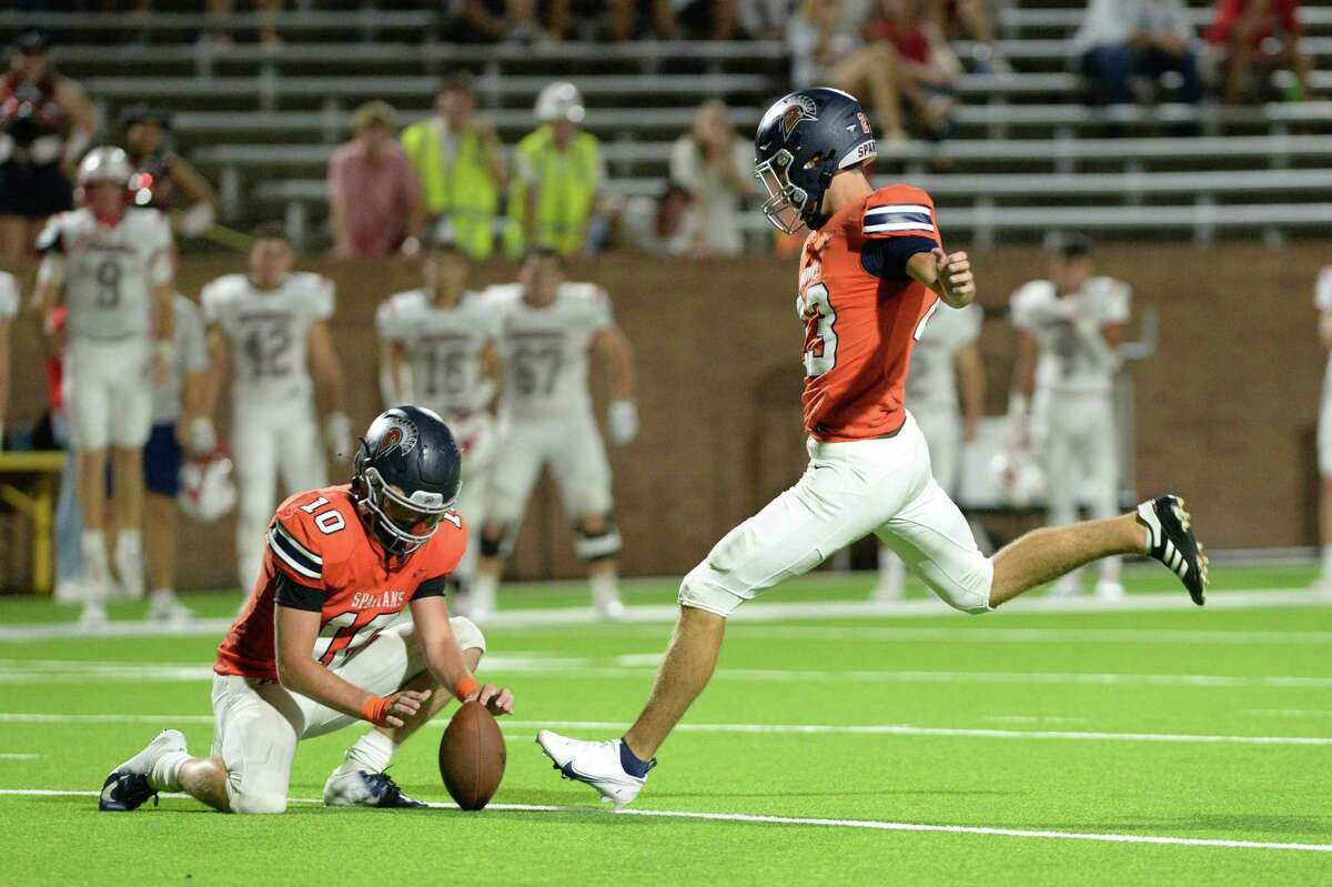 Scott Stanford (10) of Seven Lakes holds the ball for a game-winning field goal by Keegan Sneedon (23) in the final 3 seconds of a non-District football game between the Seven Lakes Spartans and the Memorial Mustangs on Friday, August 27, 2021 at Rhodes Stadium, Katy, TX.