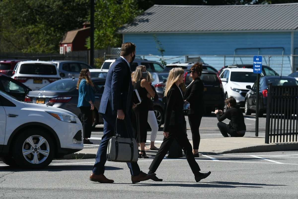 Schoharie County District Attorney Susan Mallery, at right, walks past family and friends of those killed in the Oct. 6, 2018 limousine crash in Schoharie. They crowd gathered outside the Schoharie school building where the operator of the limousine company, Nauman Hussain, 31, pleaded guilty on Sept. 2, 2021 to charges of criminally negligent homicide in a plea deal that will spare him prison time.