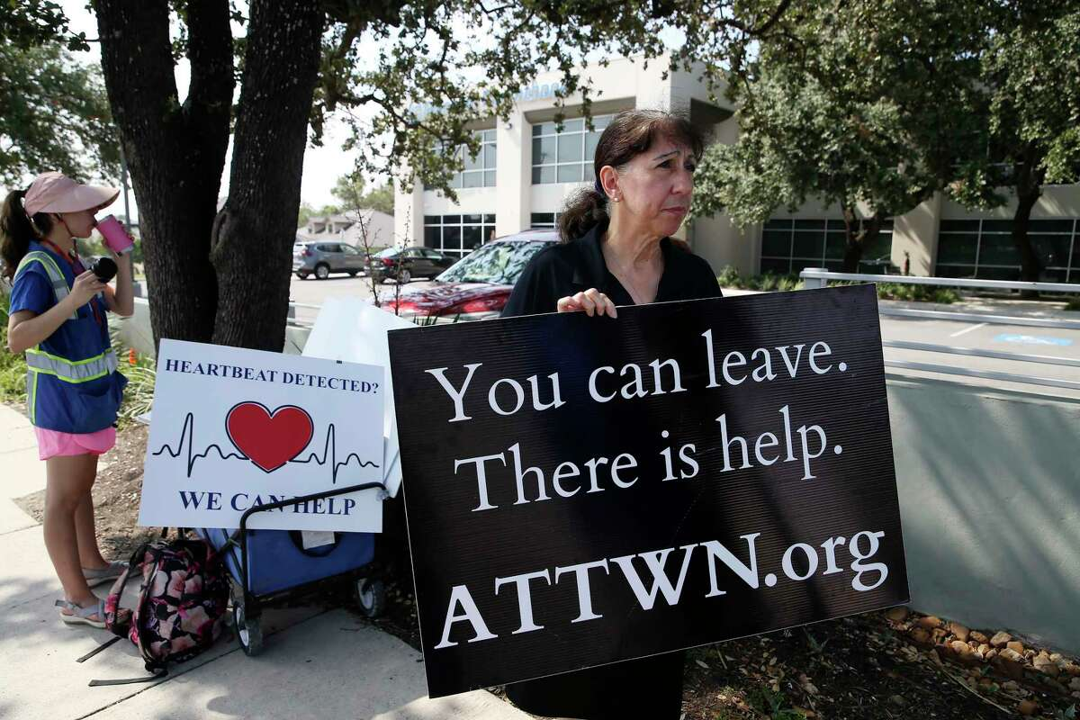 Catherine Nix, right, and Melanie Salazar of San Antonio Coalition for Life protest Wednesday outside the Planned Parenthood offices on Babcock Road.