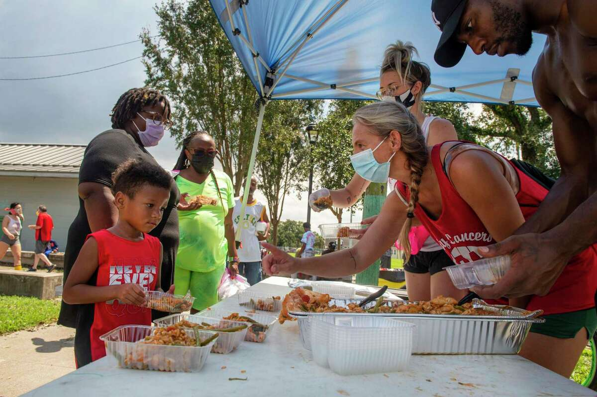 Volunteers and neighbors with the Committee for a Better New Orleans serve food in the St. Roch neighborhood of New Orleans, Tuesday, Aug. 31, 2021, two days after Hurricane Ida. World Central Kitchen along with local restaurants helped coordinate food distribution.