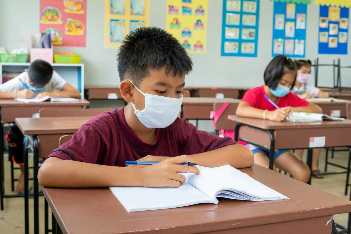 Masked student in classroom during COVID-19 pandemic.