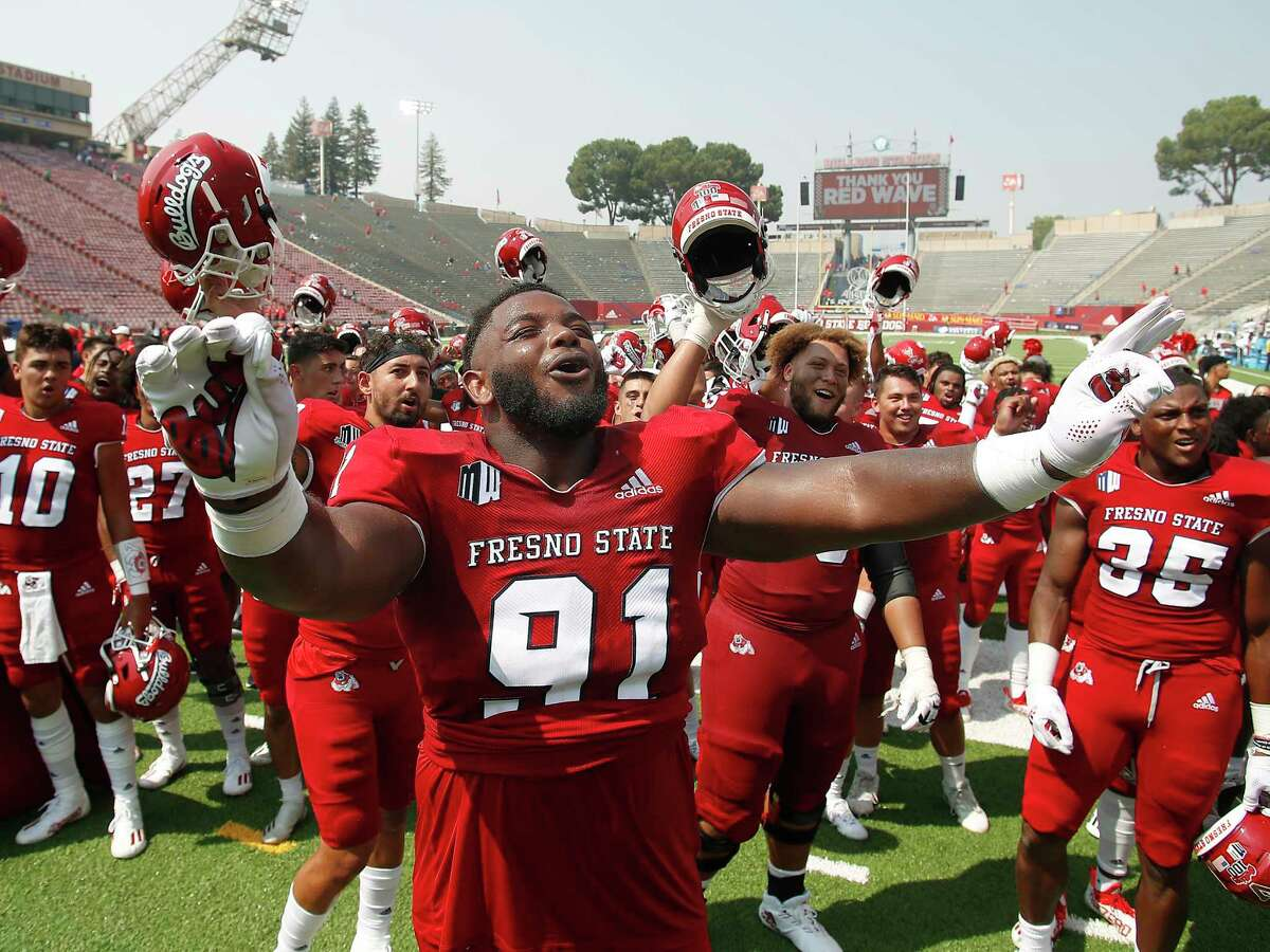 Fresno State defensive tackle Matt Lawson celebrates with the band after Fresno State defeated Connecticut in an NCAA college football game in Fresno, Calif., Saturday, Aug. 28, 2021.
