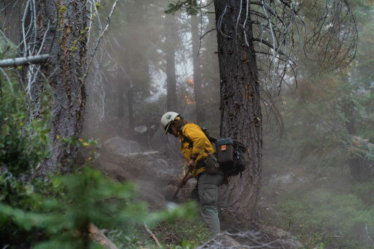 A member of the Truckee Hotshots works on a steep slope Wednesday as the Caldor Fire burns in the background near Christmas Valley close to South Lake Tahoe.