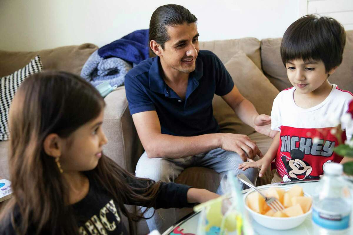 Mr. Sultani plays with his children, Uzma, 7 (left), and Edris, 3, at their home in Milpitas. The family traveled to Afghanistan in June to visit a sick family member and then struggled to leave as the country fell under Taliban control.