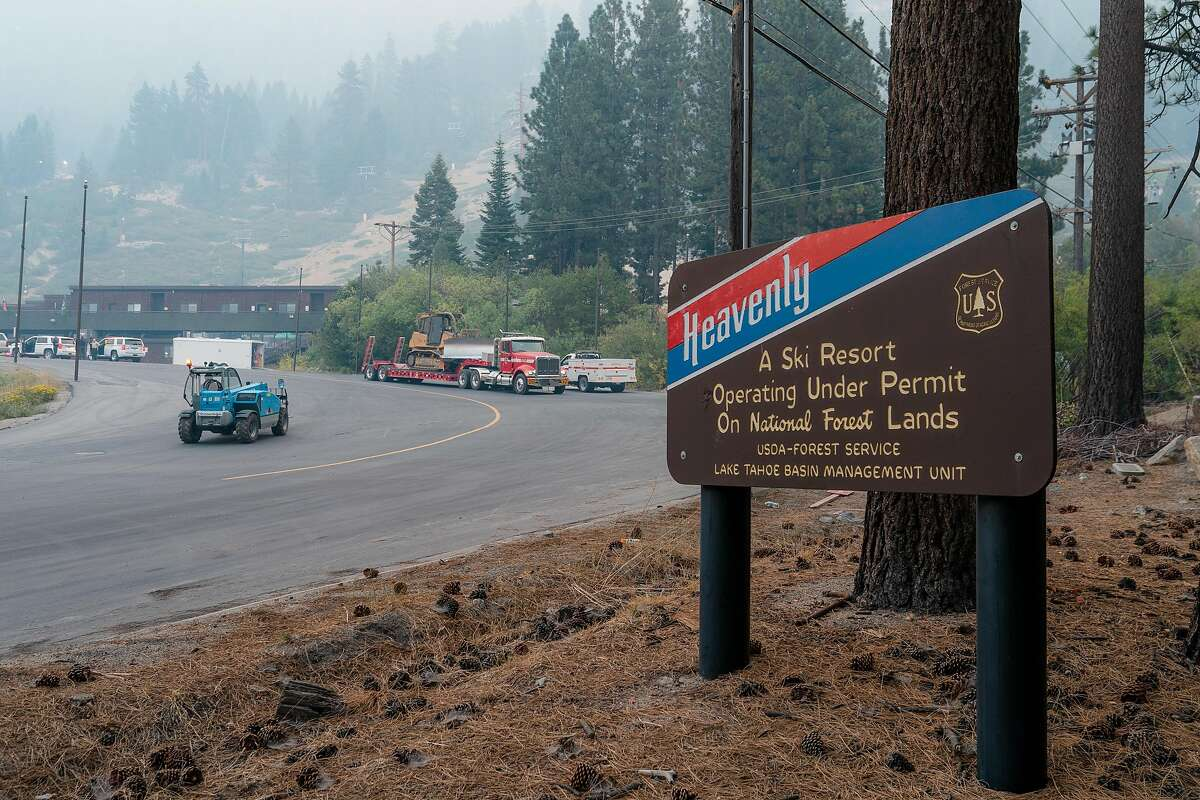 A sign for Heavenly Ski Resort stands at the entrance to the parking lots where CalFire crews have been loading dozers as a maintenance vehicle drives by in South Lake Tahoe, Calif., on Wednesday, September 1, 2021.