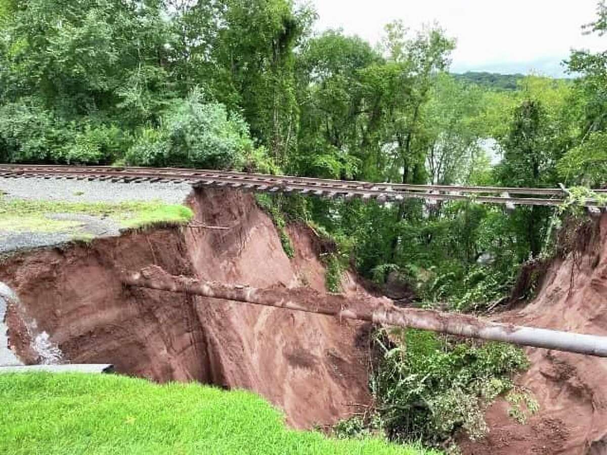 A massive sinkhole opened up near the 13th hole at the TPC River Highlands in Cromwell following storm Ida, leaving the railroad tracks in the air and a Buckeye natural gas pipeline exposed.