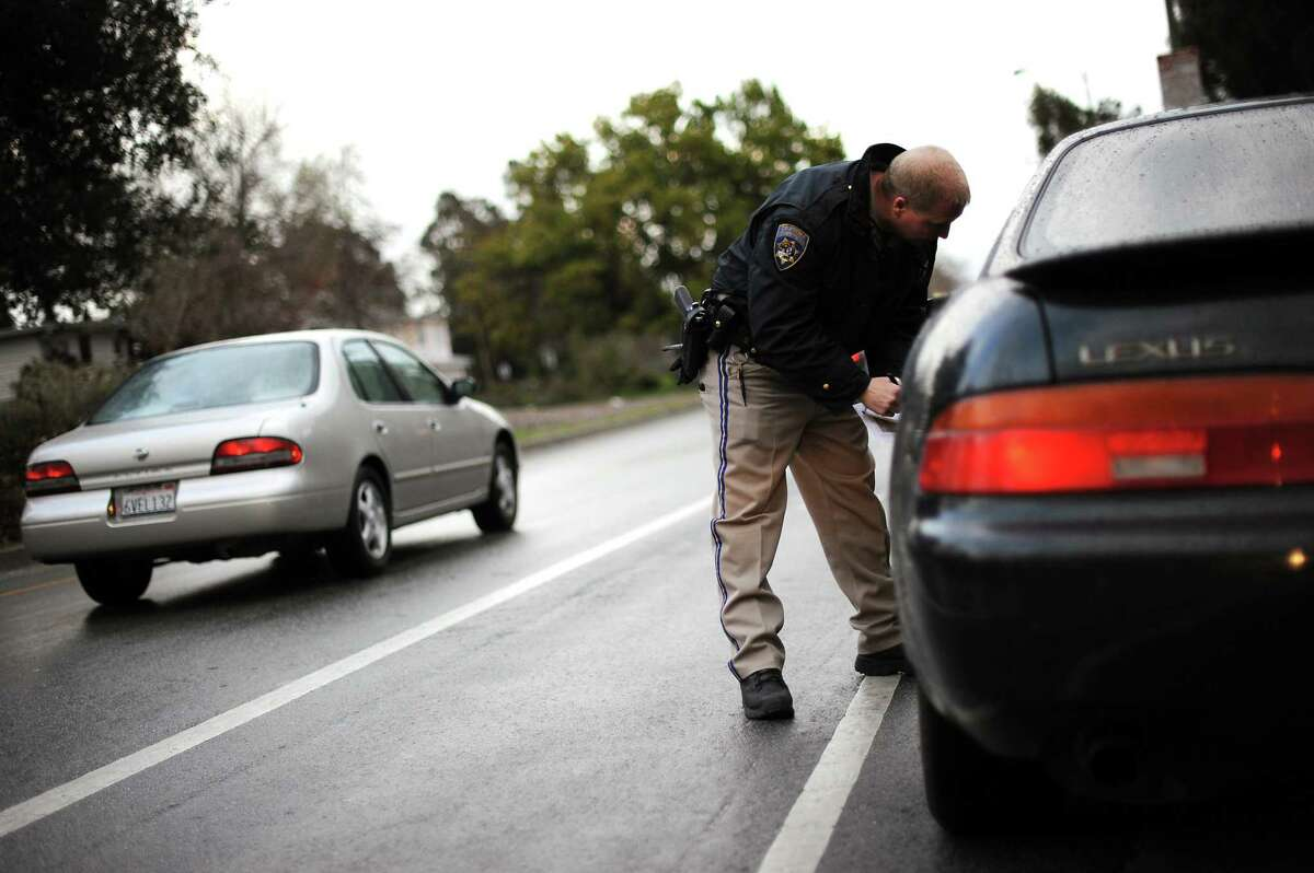 A California Highway Patrol officer speaks with a driver during a check for a seat belt violation and DUI check.
