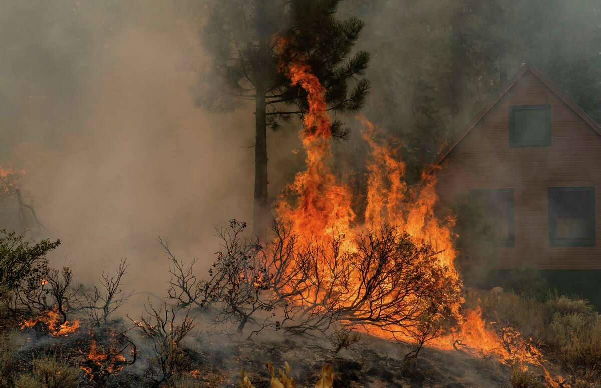 Brush burns during a structure protection operation in Christmas valley, near Heavenly Ski Resort in South Lake Tahoe, Calif., on Wednesday, September 1, 2021.