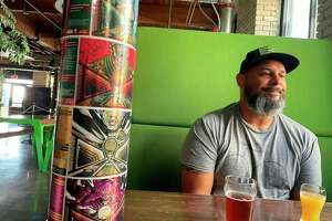 City Built owner Edwin Collazo enjoys a minute with some fresh beer, and a stack of upcoming labels at his brewery located in Grand Rapids. (Amy Sherman/ForMI Brew Trail)