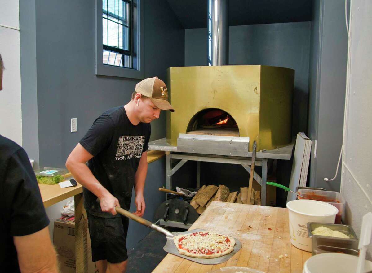 Kyle MacPherson with DeFazio's Pizzeria gets set to place a pie into the wood fired pizza oven at the new DeFazio's Pizzeria location on Thursday, Sept. 2, 2021, in Albany, N.Y.