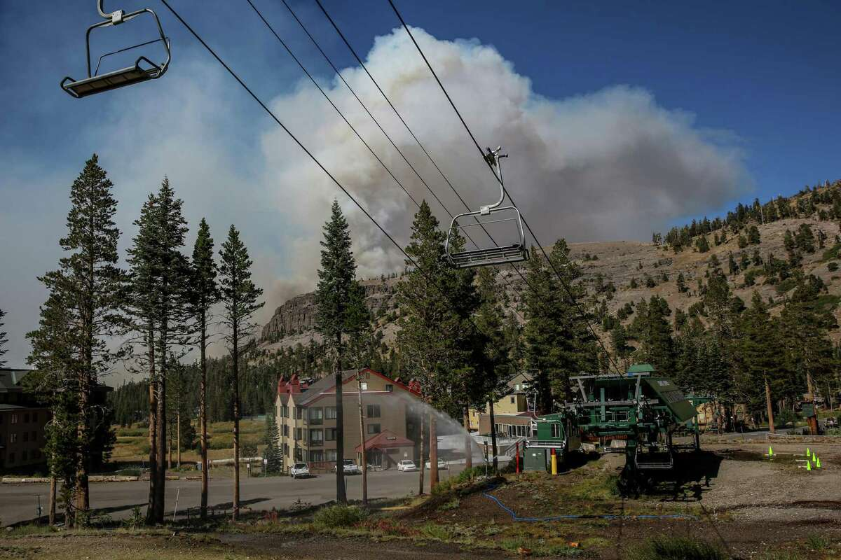 As smoke from the Caldor Fire rises over a ridge, a sprinkler blasts water toward the ski lift at Kirkwood Mountain Resort on Wednesday.