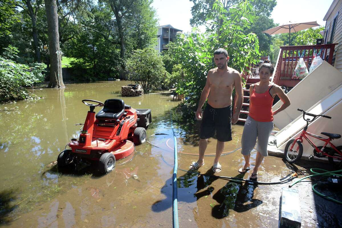 Dave and Christina Ramos stand in the remaining flood waters in the backyard of their home on Renwick Place, in Bridgeport, Conn. Sept. 2, 2021. The Ramos' neighborhood was flooded when heavy rains brought in from the remnants of Hurricane Ida caused flooding along the Rooster River.