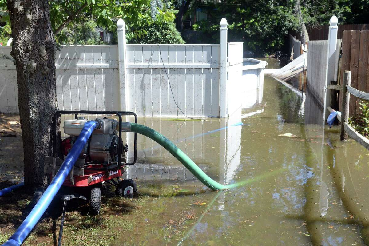 Pumps continue to drain water from a flooded backyard behind a home on Renwick Place, in Bridgeport, Conn. Sept. 2, 2021. The neighborhood was flooded when heavy rains brought in from the remnants of Hurricane Ida caused flooding along the Rooster River.