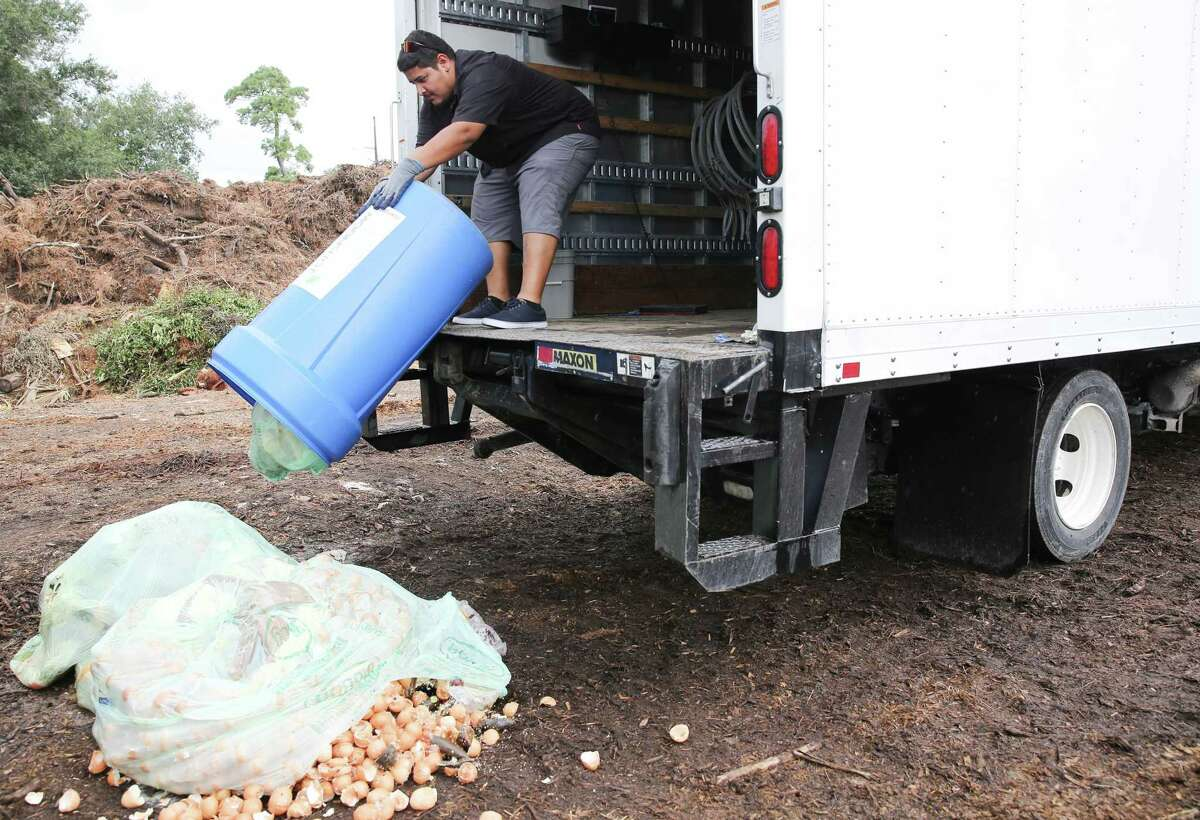 Cristian Flores, an employee with Moonshot, dumps restaurant food waste at Nature's Way Resources, in Conroe on Wednesday, Aug. 18, 2021. Moonshot, a company that picks up compost from homes and businesses takes their food scraps to Nature's Way Resources.