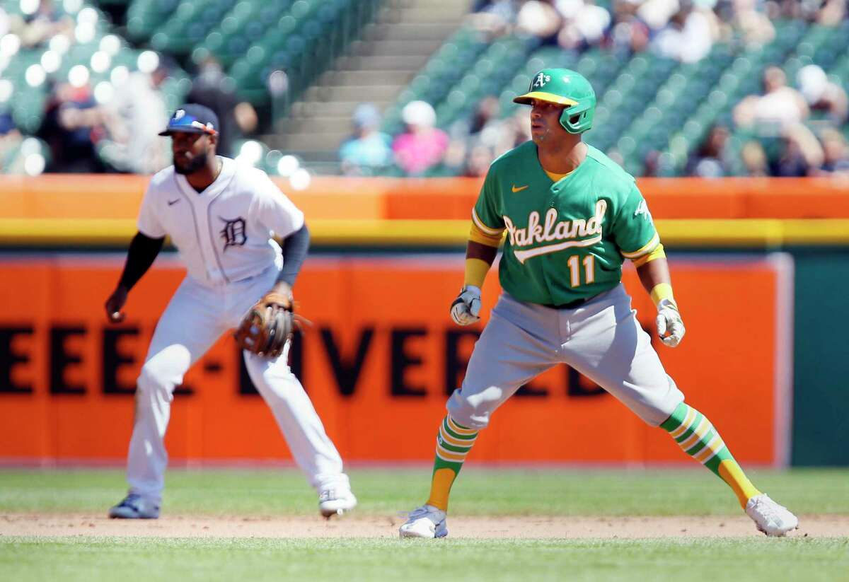 Oakland Athletics' Khris Davis (11) leads off second base next to Detroit Tigers shortstop Niko Goodrum after hitting a ground-rule double to drive in one run during the fourth inning of a baseball game Thursday, Sept. 2, 2021, in Detroit. (AP Photo/Duane Burleson)