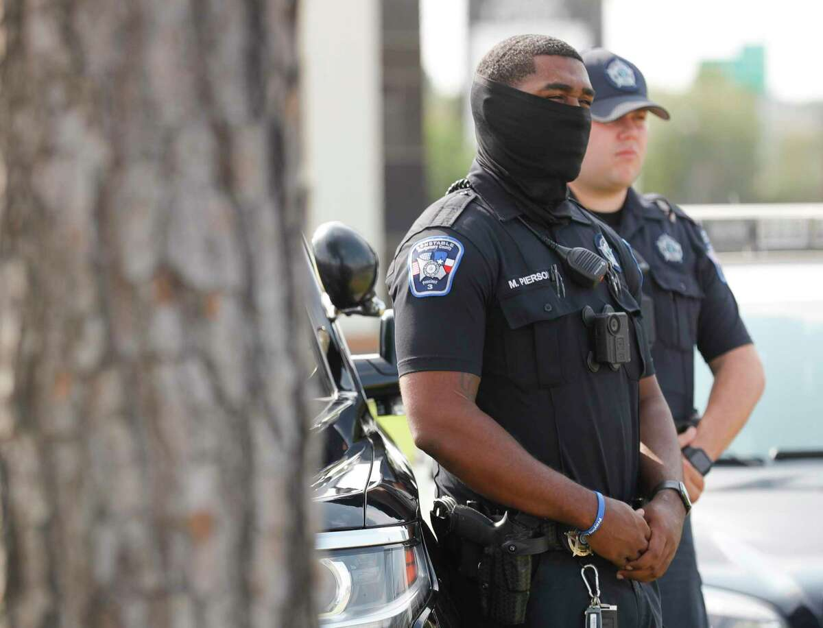 A Montgomery County Precinct 3 Constable wears a face covering while listens during a press conference on DWI enforcement.