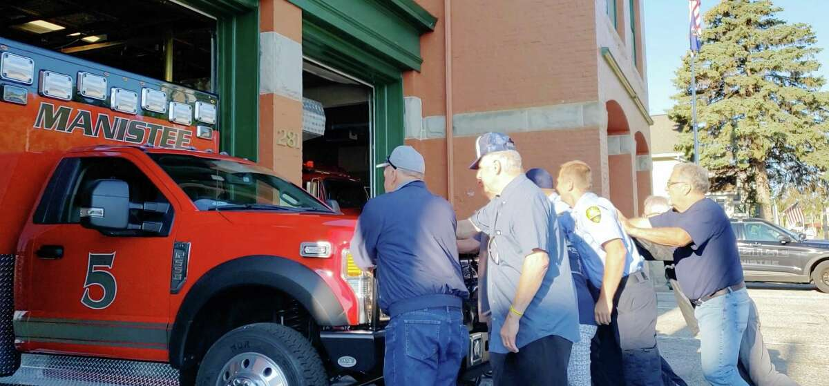Manistee City Fire Department firefighter-paramedics as well as retired personnel and Manistee City Council members were at the department on First Street helping to push the shining new PL Customambulance into its new position on Thursday morning. (Arielle Breen/News Advocate)