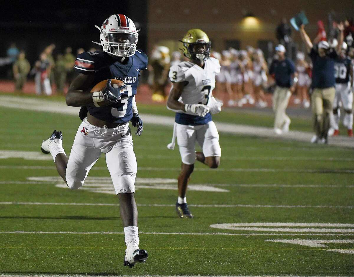 Atascocita defensive back Bennie Qualls, left, runs his interception for a touchdown past Klein Collins wide receiver Marquel Allen during the first half of a high school football game, Thursday, Aug. 26, 2021, in Humble.