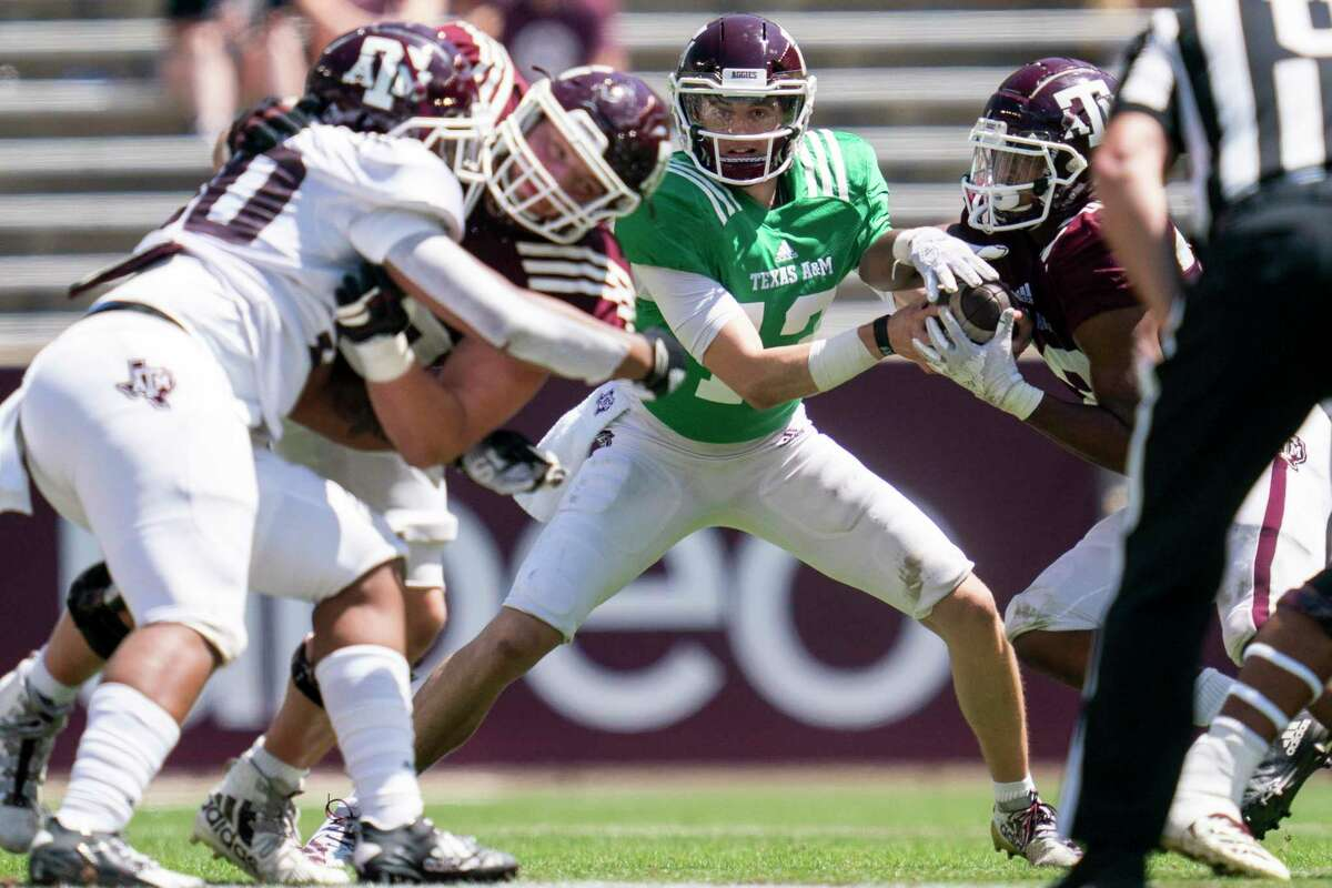 Texas A&M quarterback Haynes King (13) fakes a hand off before running a bootleg play during the Texas A&M Maroon and White Spring game in College Station