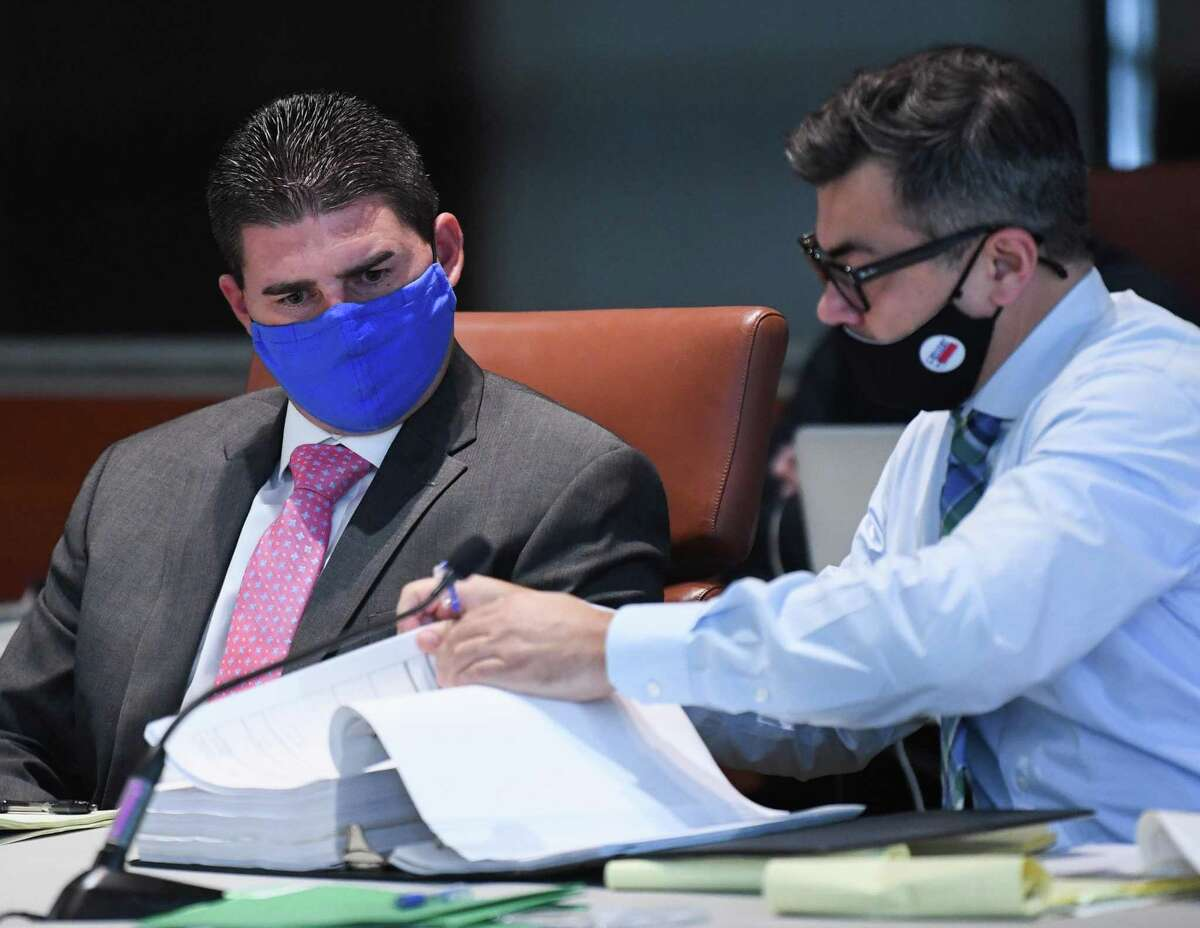 Fired San Antonio Police Detective Daniel Pue, left, and his attorney, Ricardo Garcia, look through a notebook from the investigation against him during an arbitration hearing on Thursday, Sept. 2, 2021. Pue, who is accused of repeatedly hitting a woman, is seeking reinstatement through arbitration.