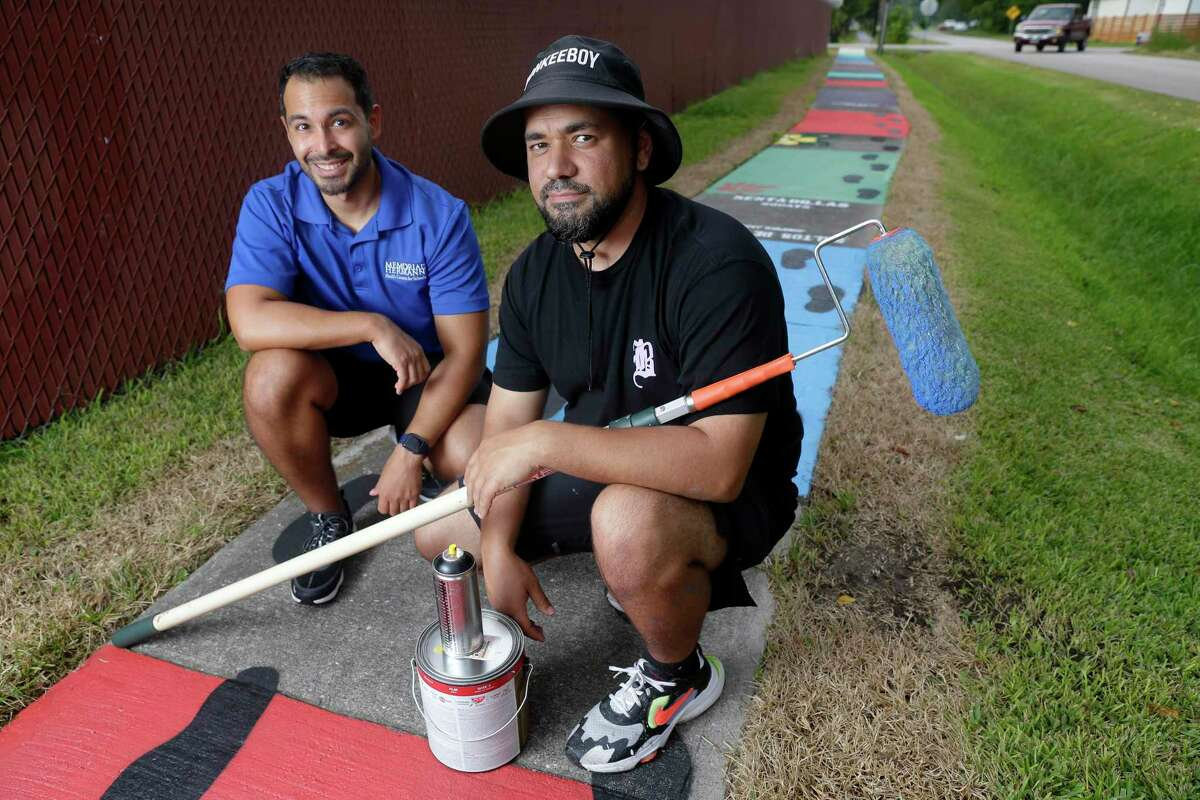 """Jorge Sanchez, left, Memorial Hermann project lead, and artist Alex """"Donkeeboy"""" Roman, right, with the sidewalk artwork by Roman along Highlawn Street, just off Tidwell Road in the Northline neighborhood Wednesday, Sep. 1, 2021 in Houston, TX. Since 2017 Memorial Hermann has focused on improving the health of Northline Community residents by promoting park usage, safety and exercise."""