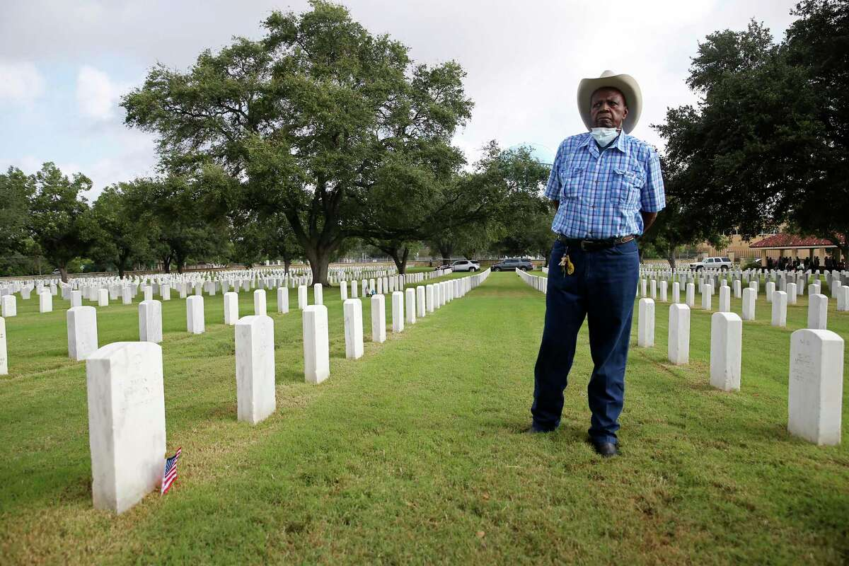 """Bexar County Buffalo Soldiers' Billy Gordon, 79, places U.S. flags by the headstone of black soldiers at Fort Sam Houston National Cemetery, Thursday, Sept. 2, 2021. As part of it's Black History Film Series, the San Antonio African American Community Archive and Museum will present """"The 24th,"""" a film directed by Oscar winner Kevin Willmott. The film tells the story of soldiers from the all-Black 24th Infantry who were put on trial for a riot in Houston in 1917 that resulted in the deaths of 16 white locals and five Black soldiers. Thirteen Black soldiers were found guilty and sentenced to death. The soldiers were hanged near Salado Creek and buried at Fort Sam Houston National Cemetery."""