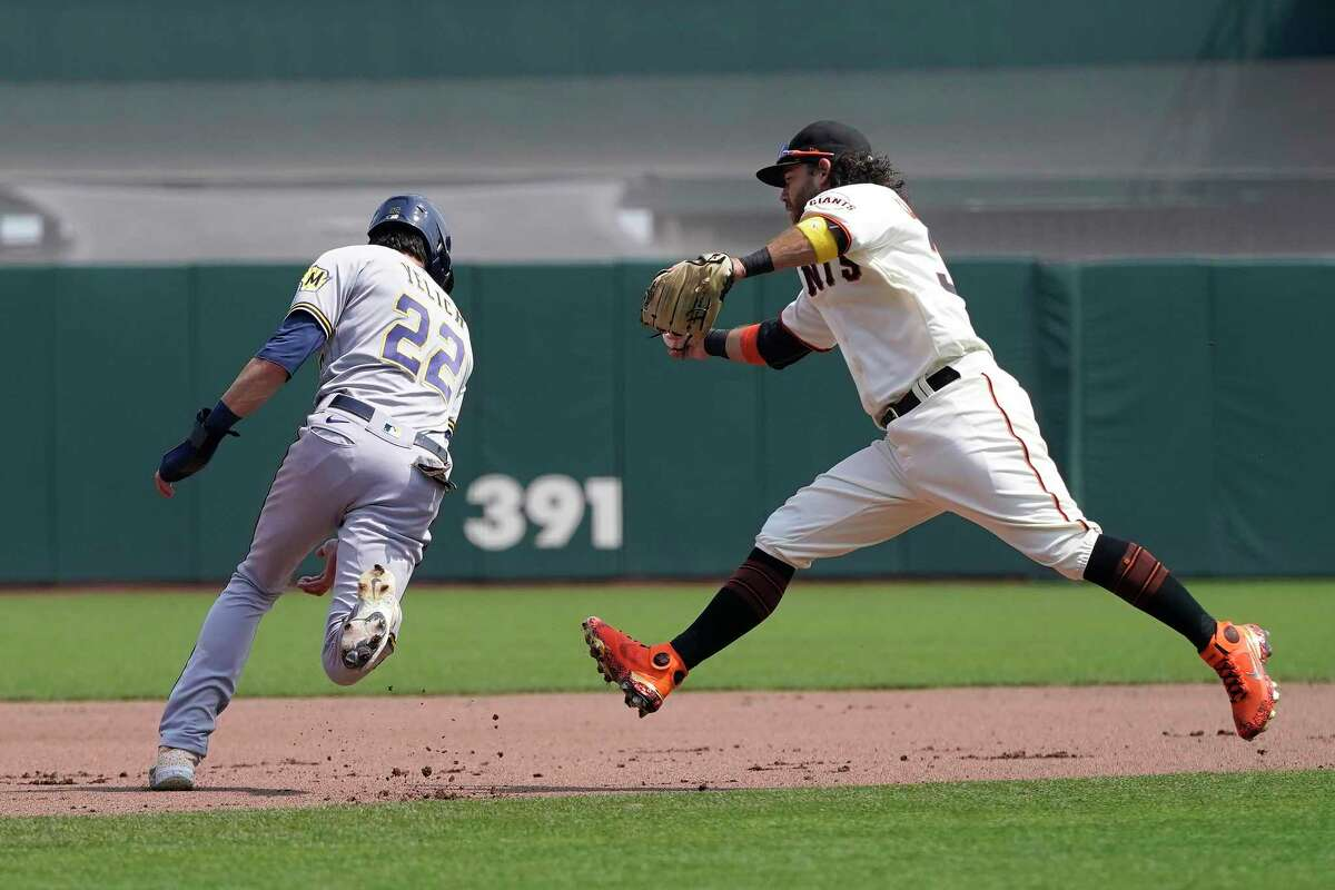 San Francisco Giants' Brandon Crawford, right, reaches to tag out Milwaukee Brewers' Christian Yelich trying to advance to third base on a single by Jace Peterson during the fourth inning of a baseball game in San Francisco, Thursday, Sept. 2, 2021. (AP Photo/Jeff Chiu)
