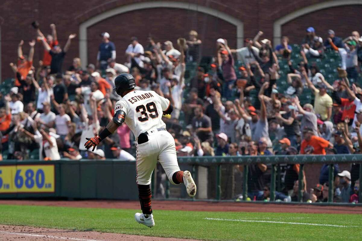 Fans cheer as San Francisco Giants' Thairo Estrada (39) rounds the bases after hitting a three-run home run against the Milwaukee Brewers during the eighth inning of a baseball game in San Francisco, Thursday, Sept. 2, 2021. (AP Photo/Jeff Chiu)