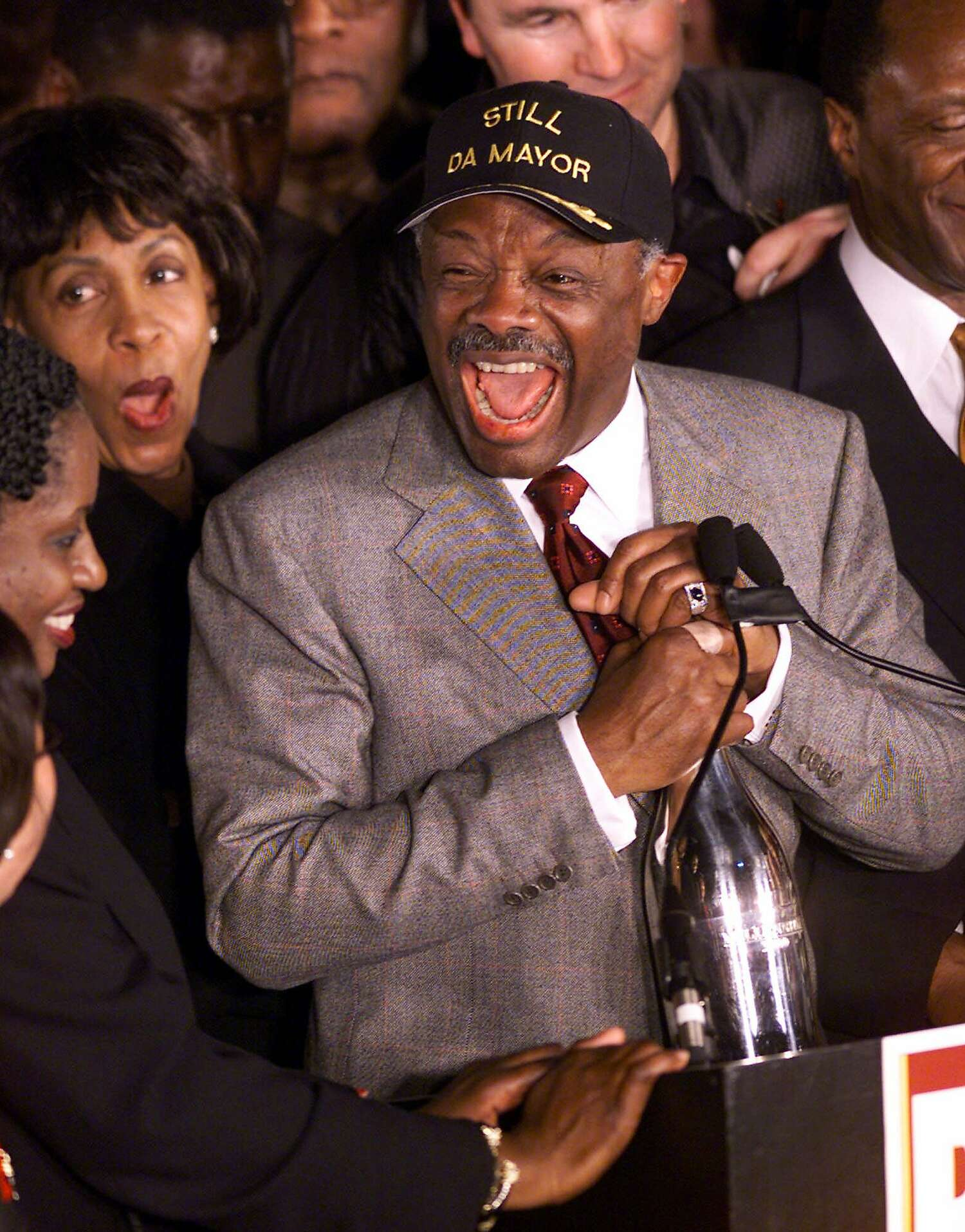 """San Francisco Mayor Willie Brown wears a gray suit and a hat that says """"Still Da Mayor"""" while holding a bottle of Champagne surrounded by supporters in 1999."""