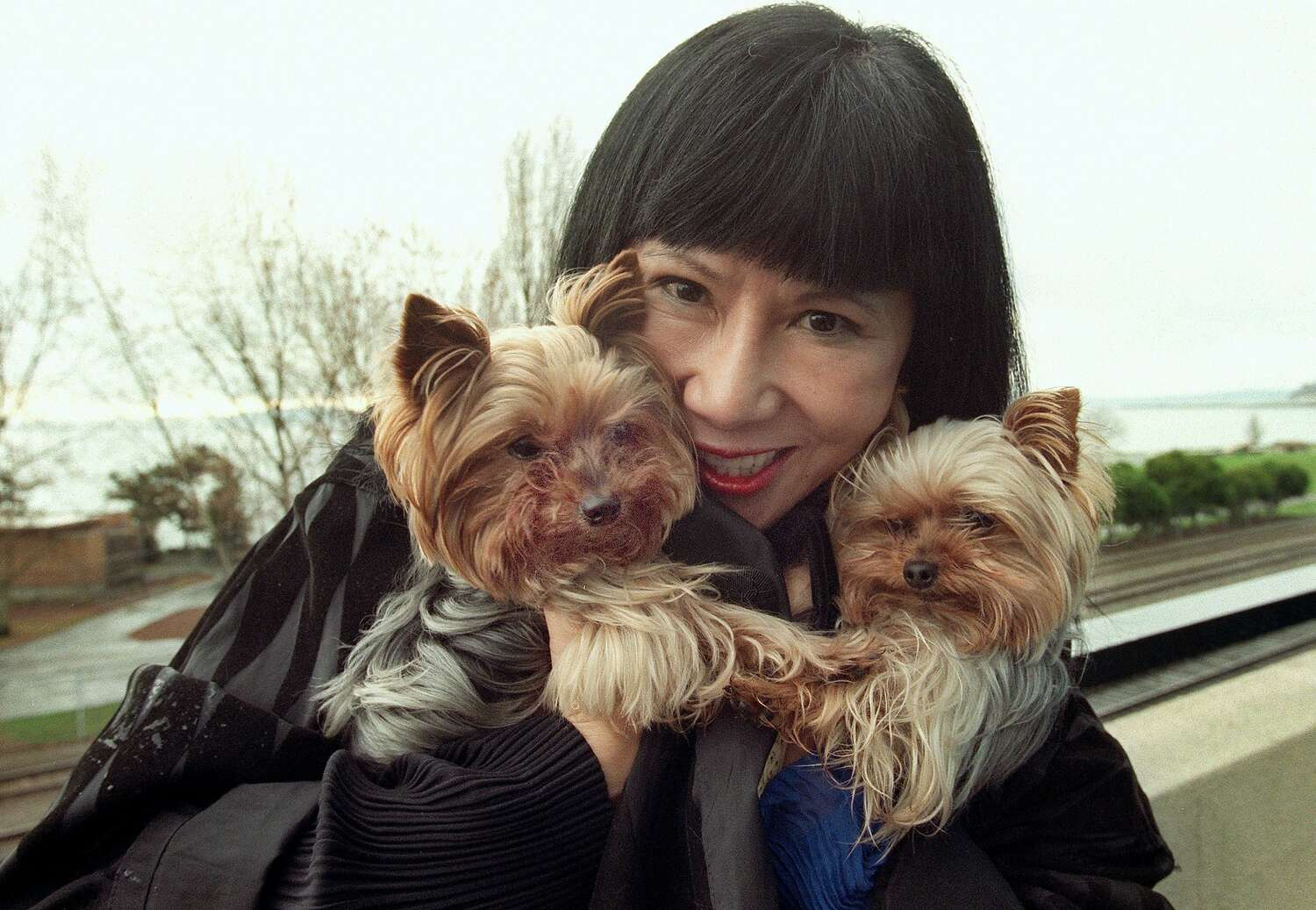 Author Amy Tan smiles and holds her two Yorkshire terriers in March 2001.