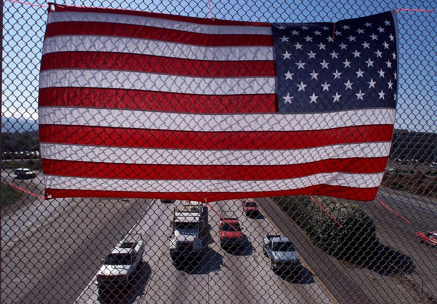 An American flag is strung to a chainlink fence along Santa Rita Rd. above the I-580 in Pleasanton.