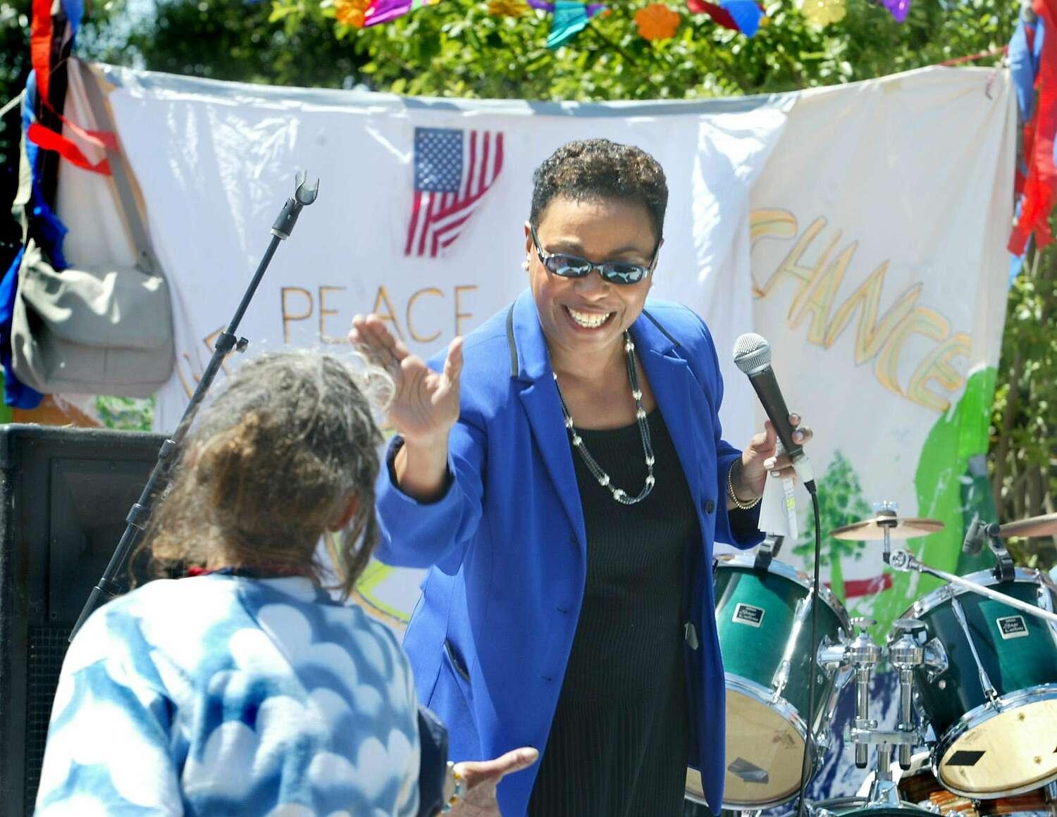 U.S. Rep. Barbara Lee holds a microphone and smiles as she gives a low-five to a person after a speech in Berkeley, Calif. in 2003.