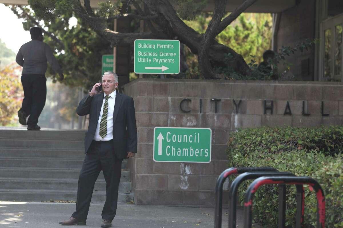 Former Santa Clara City Attorney Brian Doyle talks to his lawyer on the phone outside Santa Clara City Hall on Thursday.