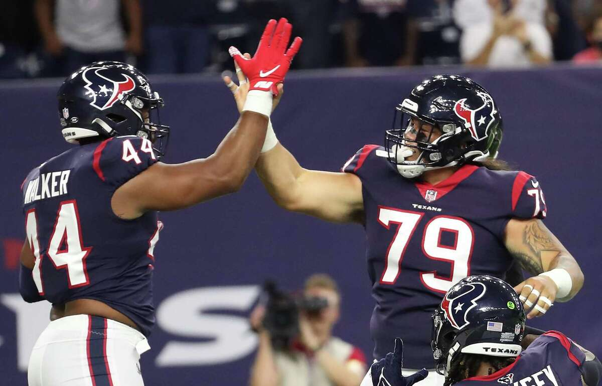 Texans defensive end DeMarcus Walker, left, and defensive tackle Roy Lopez celebrate a sack of Buccaneers quarterback Blaine Gabbert that resulted in a safety in the preseason finale at NRG Stadium.
