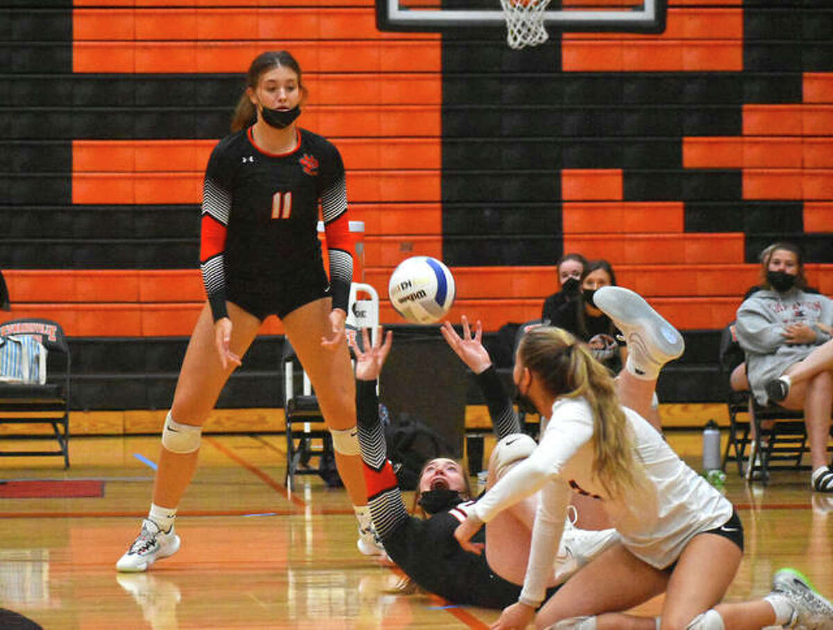 Edwardsville setter Lexie Griffin keeps the play alive from her back as libero Kaitlyn Conway and Gabby Saye watch on in the second game against Collinsville on Thursday inside Lucco-Jackson Gymnasium.