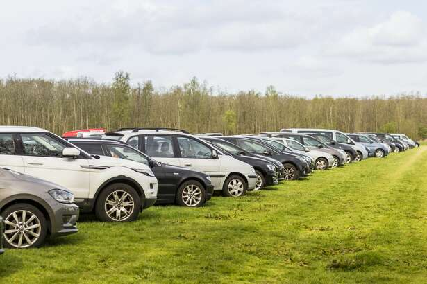 Cars parked outside the Keukenhof on a large field of grass.